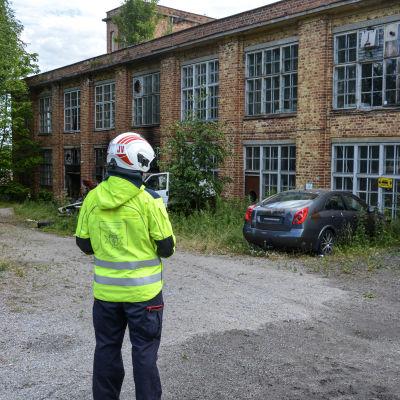 Ryggen av person i räddningsverkets kläder som betraktar gammal byggnad som brunnit.