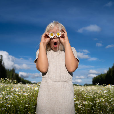 Tyttö hassuttelee päivänkakkarat silmillään.