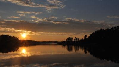 Ett spegelblankt hav med en sol som ligger strax ovanför horisonten och som speglar sig i havet. Öarna bildar svarta silhuetter.