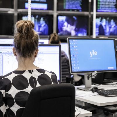 En kvinna arbetar vid datorn på Yle Uutisets nyhetsredaktion.