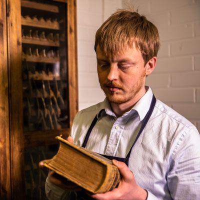 Kuvassa kirjansitoja Lappalainen pitää vanhaa kirjaa kädessään.