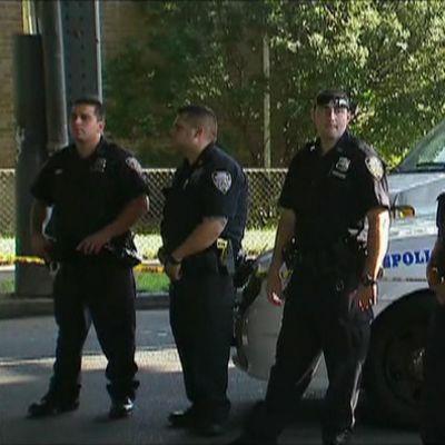 Neljä poliisia ja poliisiauto.