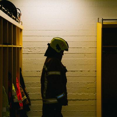 Palolaitoksen pukuhuoneessa seisoo henkilö palopuku päällä.