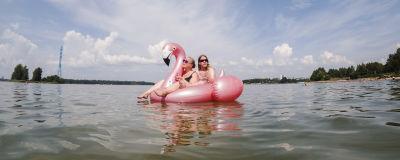 Två människor på en en uppblåsbar flamingo-badring.