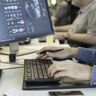 Graafikon työpisteeltä kuvattu kädet näppäimistöllä.