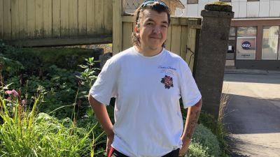 """En ung man med vit t-skjorta står på en gård med blommor. Bakom ett hus med skyltfönster där det står """"Eezy vapaus työhön""""."""