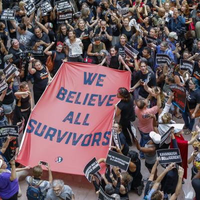 """""""Vi tror på alla överlevare"""" står det på en av de banderoller som demonstranterna hade med sig inne i en av senatsbyggnaderna."""