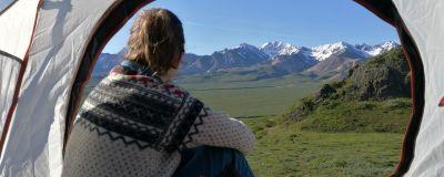 Nainen katsoo teltan oviaukosta ulos, taustalla vuoret