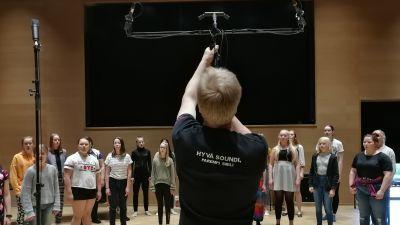 Äänittäjä Matti Heinonen asentaa mikrofoneja kuoron edessä.
