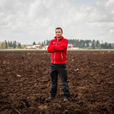 Viljelijä Ville Junnila seisoo pelloillaan.