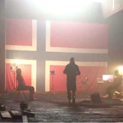 Kolme ihmistä pimeässä bunkkerissa, taustalla suuri Norjan lippu.