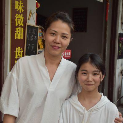 Zhou ser rakt in i kameran och ler medan hon håller om sin 10-åriga dotter som också ler mot kameran