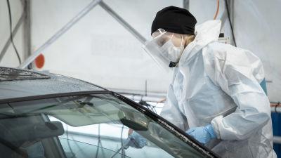 Suojavarusteisiin pukeutunut henkilö tekee koronatestiä autossa istuvalle henkilölle.