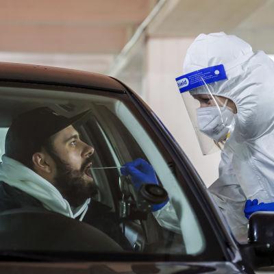 En person i skyddsutrustning tar ett coronatest på en person som sitter i en bil.