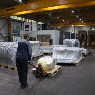 Työntekijä siirtää tavaraa teollisuushallissa.