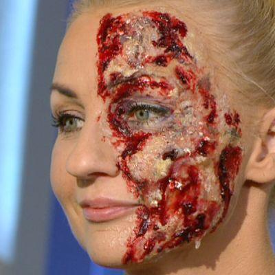 Nainen halloween-maski kasvoillaan.
