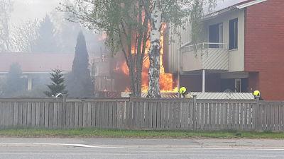 Rivitalo palaa, palomiehiä kävelee talon sivulla.