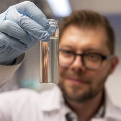 Tutkija Sami Taipale pitelee laboratoriossa käsissään pientä lasipulloa, jossa uiskentelee tutkimuksessa käytetty vesikirppu.