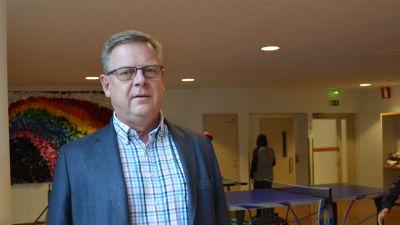 En rektor står i en skola med ett pingisbord i bakgrunden.