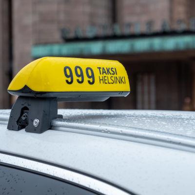Lähikuvassa taksikyltti taksin katolla.