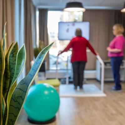 Fysioteraeutti ohjaa vanhusta tasapainopelin pelaamisessa.