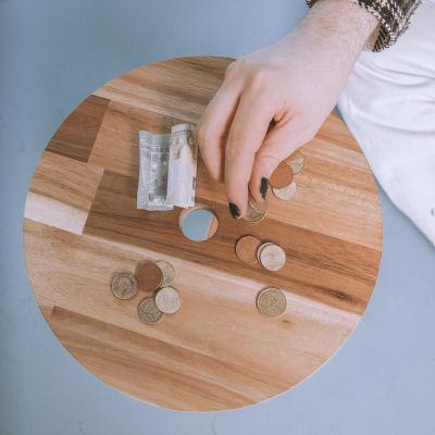 Käsi kurottamassa kolikoita pöydältä