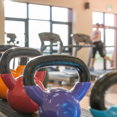I förgrunden syns vikter på ett gym, i bakgrunden en kvinna som springer på en löpmatta.