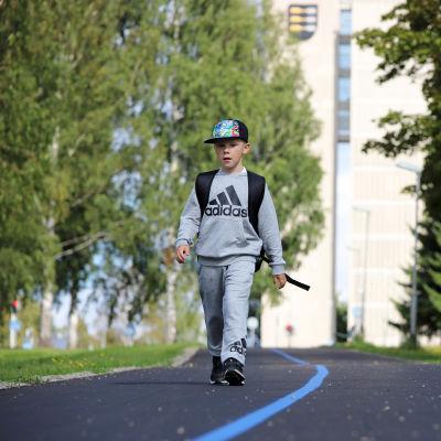 Ekaluokkalainen Nooa Sirkka kävelee turvallista koulureittiä merkkaavaa sinistä viivaa pitkin Pieksämäellä.