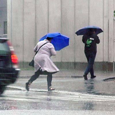 ihmisiä kävelemässä rankkasateessa
