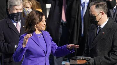 En kvinna i blålila dräkt håller handen på en Bibel som hålls av en man i svart kappa. I bakgrunden flera människor.