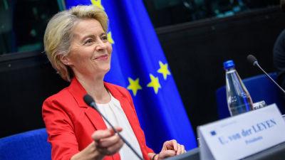 Närbild på EU-kommissionens ordförande Ursula von der Leyen vid kommissionens sammanträde i Strasbourg. I förgrunden ser vi en namnskylt och en vattenflaska, i bakgrunden den blågula EU-flaggan.