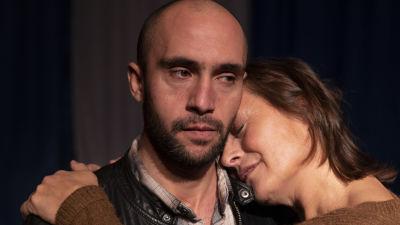 En kvinna omfamnar en man som har ett trött ansiktsuttryck.