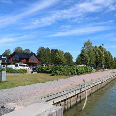 Brygga vid åkant med båtar som står förtöjda. Intill bryggan en grusväg och gräsmatta. I bakgrunden bilar och en större träbyggnad.