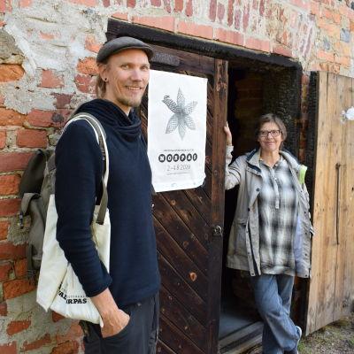 Ville Laitinen och Ritva Kovalainen vid en tegelvägg.