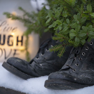 Ulkoportailla asetelma kengistä ja ikivihreistä sekä kynttilälyhdystä.