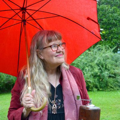 Ann-Sophie under ett rött paraply i regnet