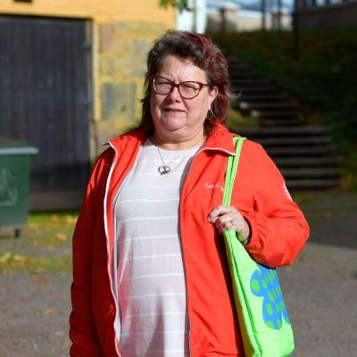En kvinna i röd jacka och glasögon utomhus. I bakgrunden en garagebyggnad.