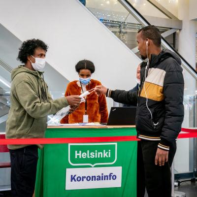 En mörkhyad man tar emot ett munskydd vid Helsingfors corona-informationspunkt i ett köpcentrum.