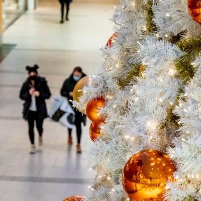 Julpynt i ett varuhus. I bakgrunden syns tre shoppare, varav två har munskydd.