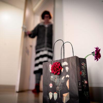 Koronakaranteenissa oleva vanhus katsoo ovelta hänelle rappuun jätettyä lahjakassia.