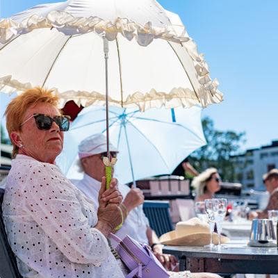 Folk under solparasoll på uteservering.