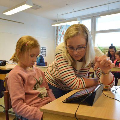 Lärare Camilla Willberg i Yttermalax skola instruerar Alwa Kinnunen i hur man använder pekplattan