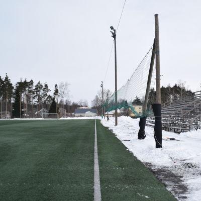 Karis konstgräsplan är grön eftersom den är uppvärmd i mars, men med snöhögar kring planen.
