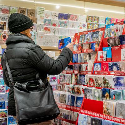 Nainen katselee joulukortteja kirjakaupassa hengityssuojain kasvoillaan.