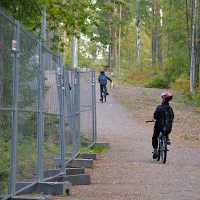 Tre barn cyklar förbi Vårberga utbildningscentrum.
