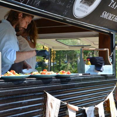 Patrik Laine serverar mat ur serveringsluckan på sin foodtruck medan en kund står bredvid och väntar.
