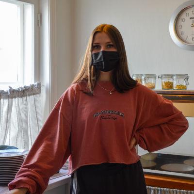 Alina Henriksson har på sig ett ansiktskydd och poserar för kameran