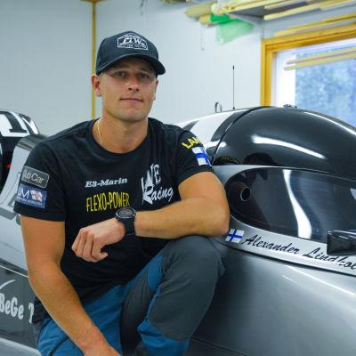 Alexander Lindholm sitter på huk vid sin gråa formel 4 racerbåt.