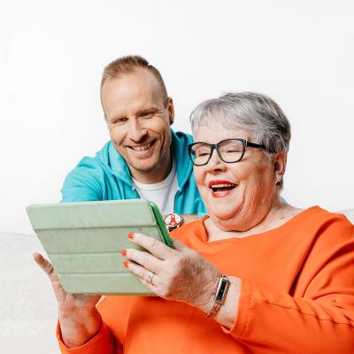 Mikko Kekäläinen ja Eila käyttävät yhdessä taulutietokonetta.