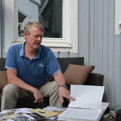 Kaj Mattsson sitter på verandan och bläddrar i en släktforskningsmapp.